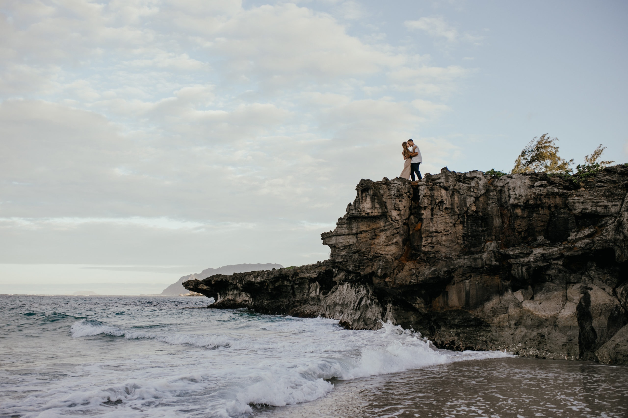 Oahu Couples Photography, far of shot of couple kissing on cliff side