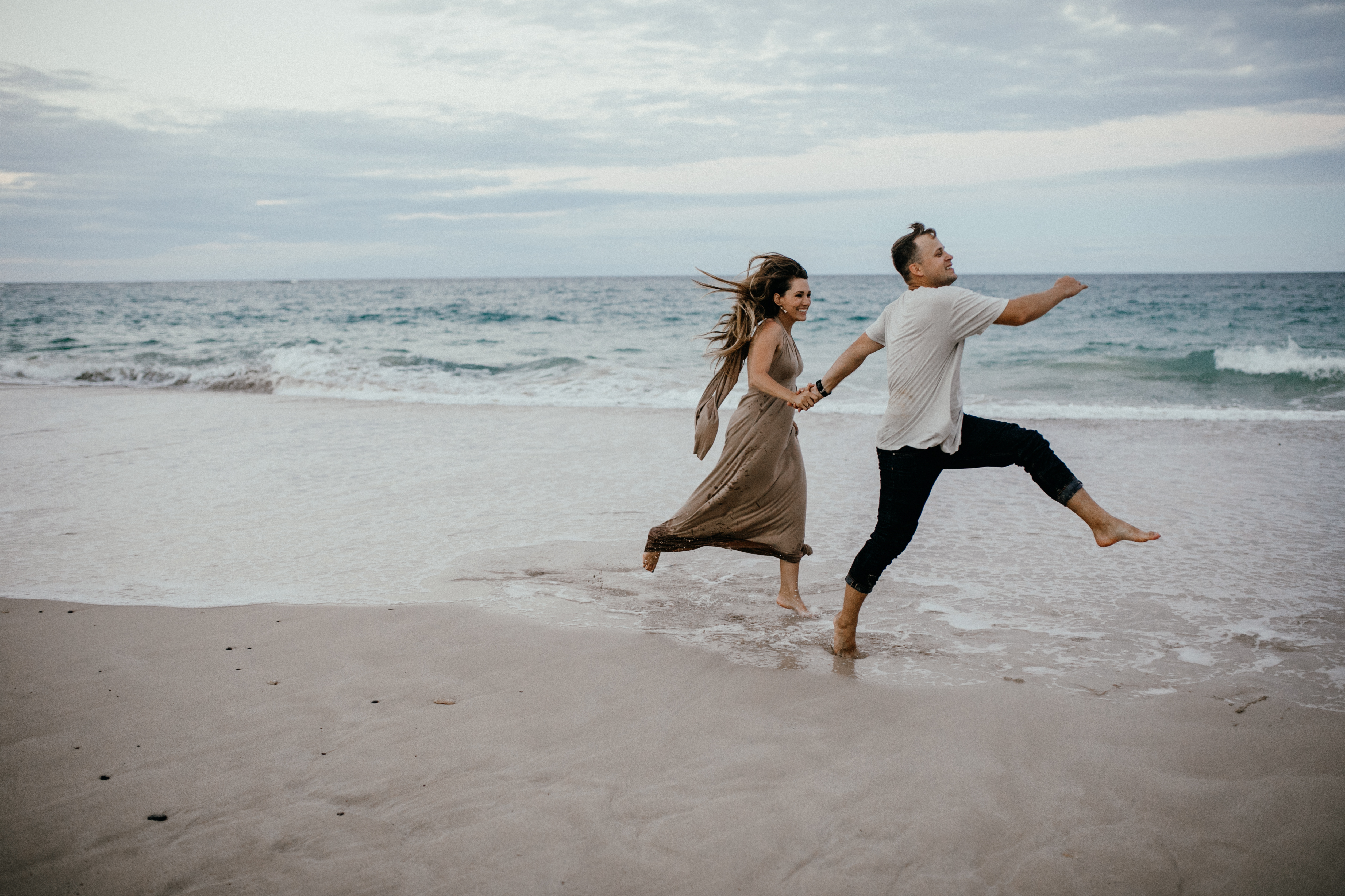 Oahu Couples Photography, couple skipping down the beach together