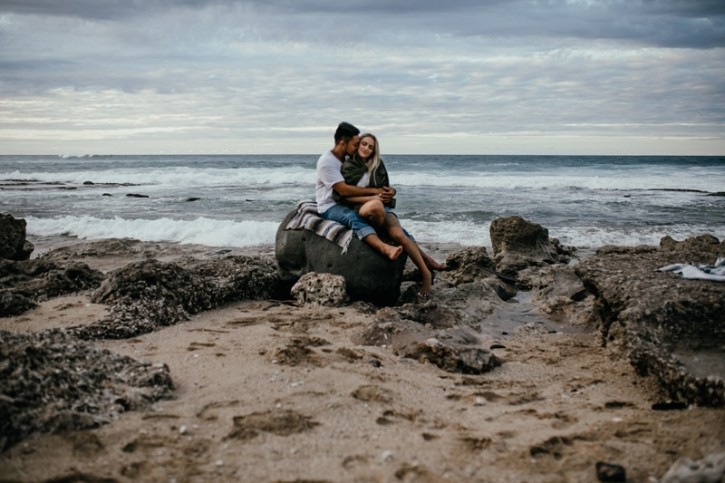 Oahu Couples Photography, man and woman cuddled up at the beach