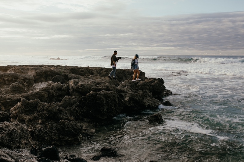 Oahu Couples Photography, wide angle of couple walking along the rocks of the beach with dog