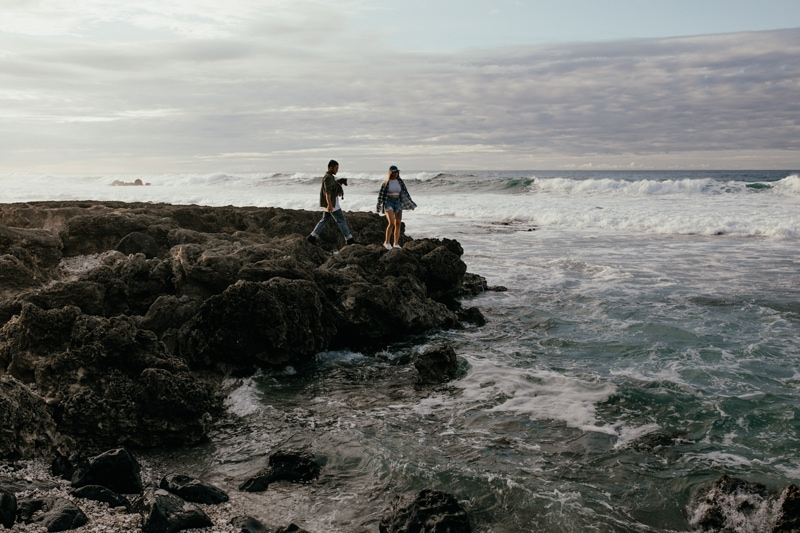 Oahu Couples Photography, couple standing on rocks next to the ocean