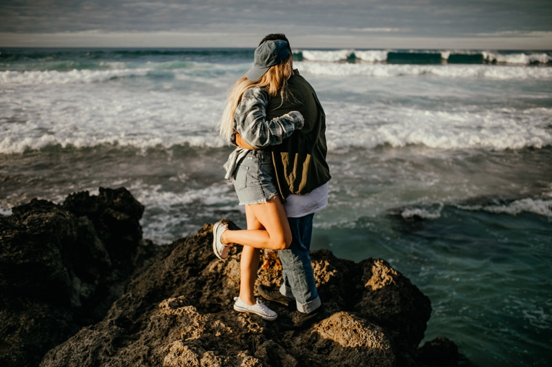 Oahu Couples Photography, couple standing and hugging next to the ocean