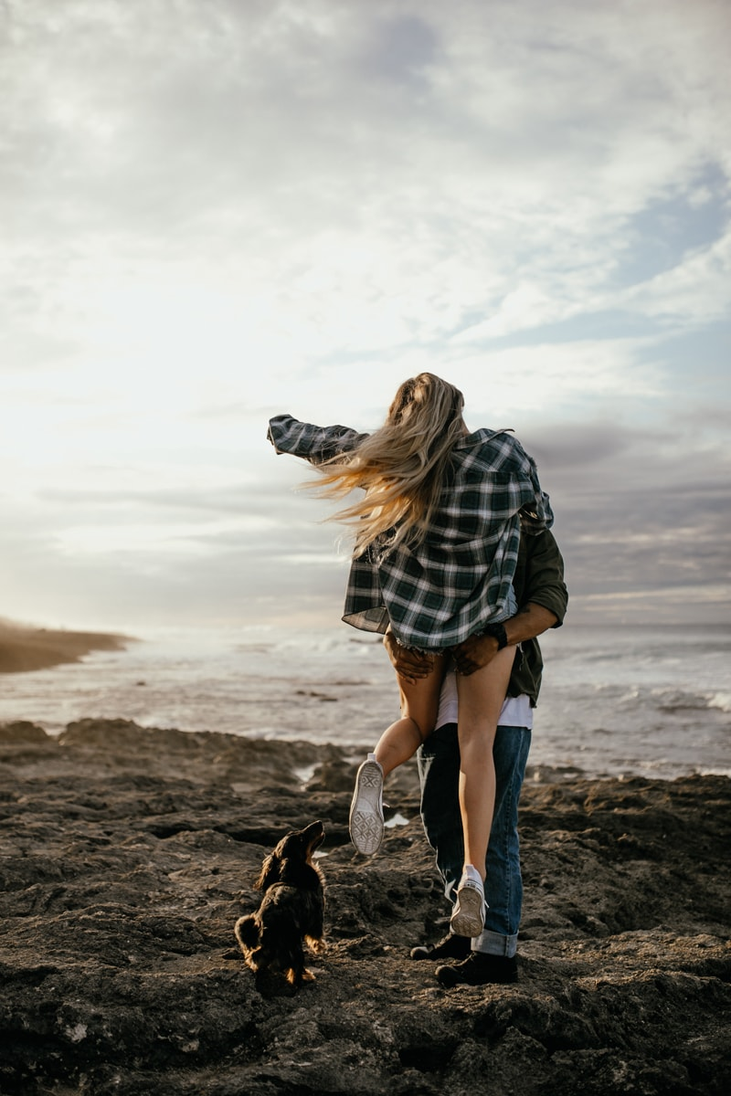 Oahu Couples Photography, man holding up woman with dog at their feet