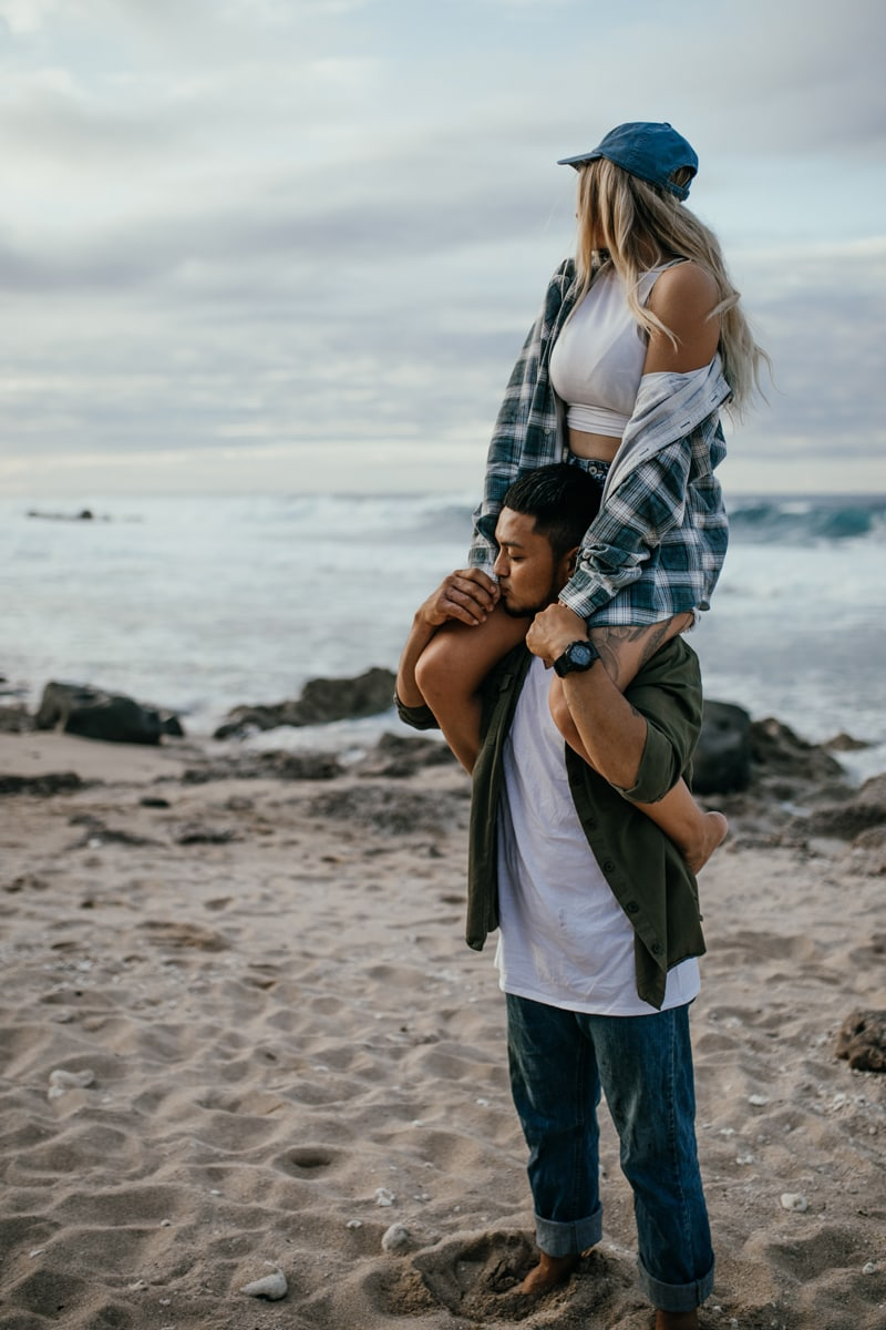 Oahu Couples Photography, woman sitting on man's shoulders looking at the water