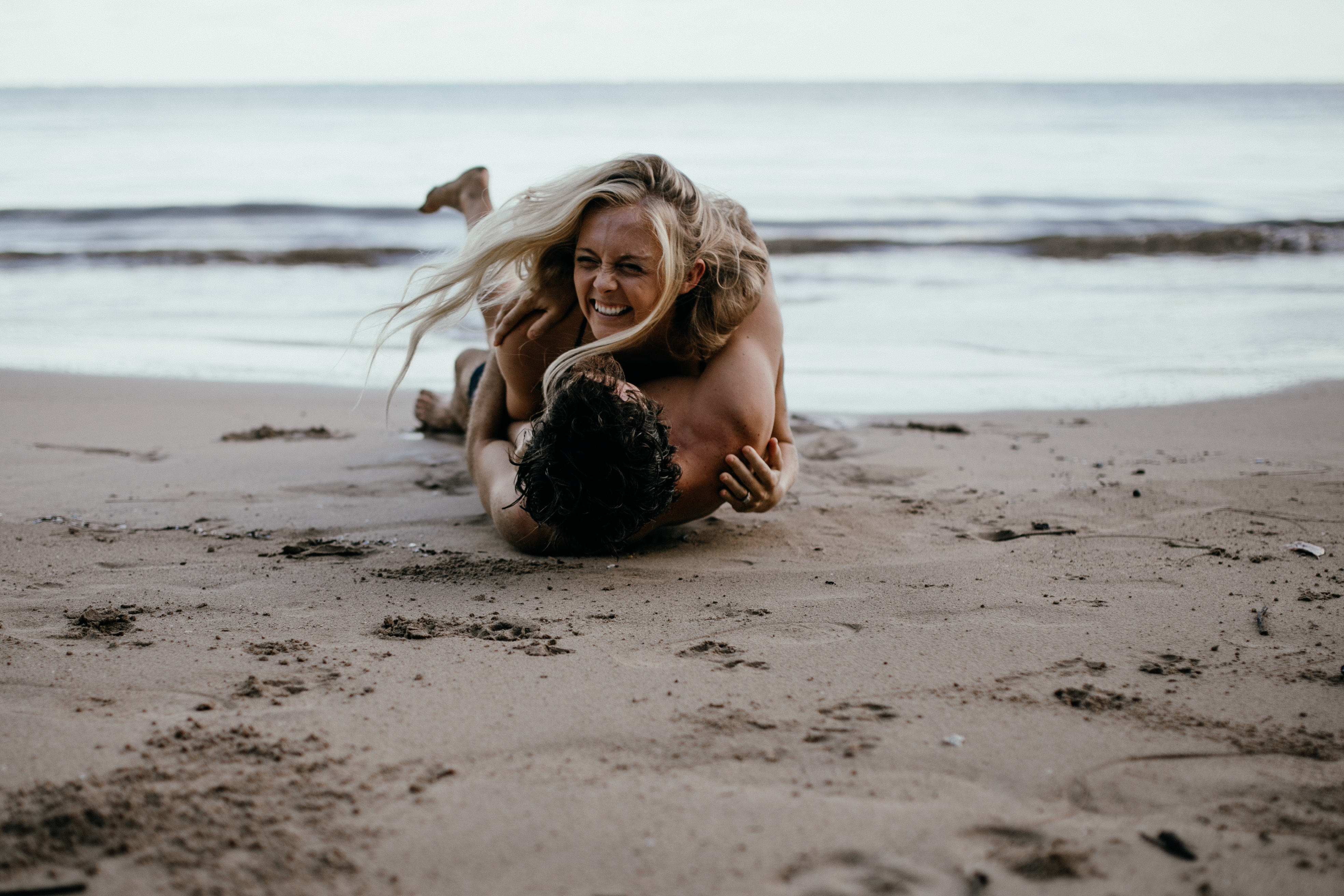 Oahu Couples Photography, couple rolling and laughing in the sand