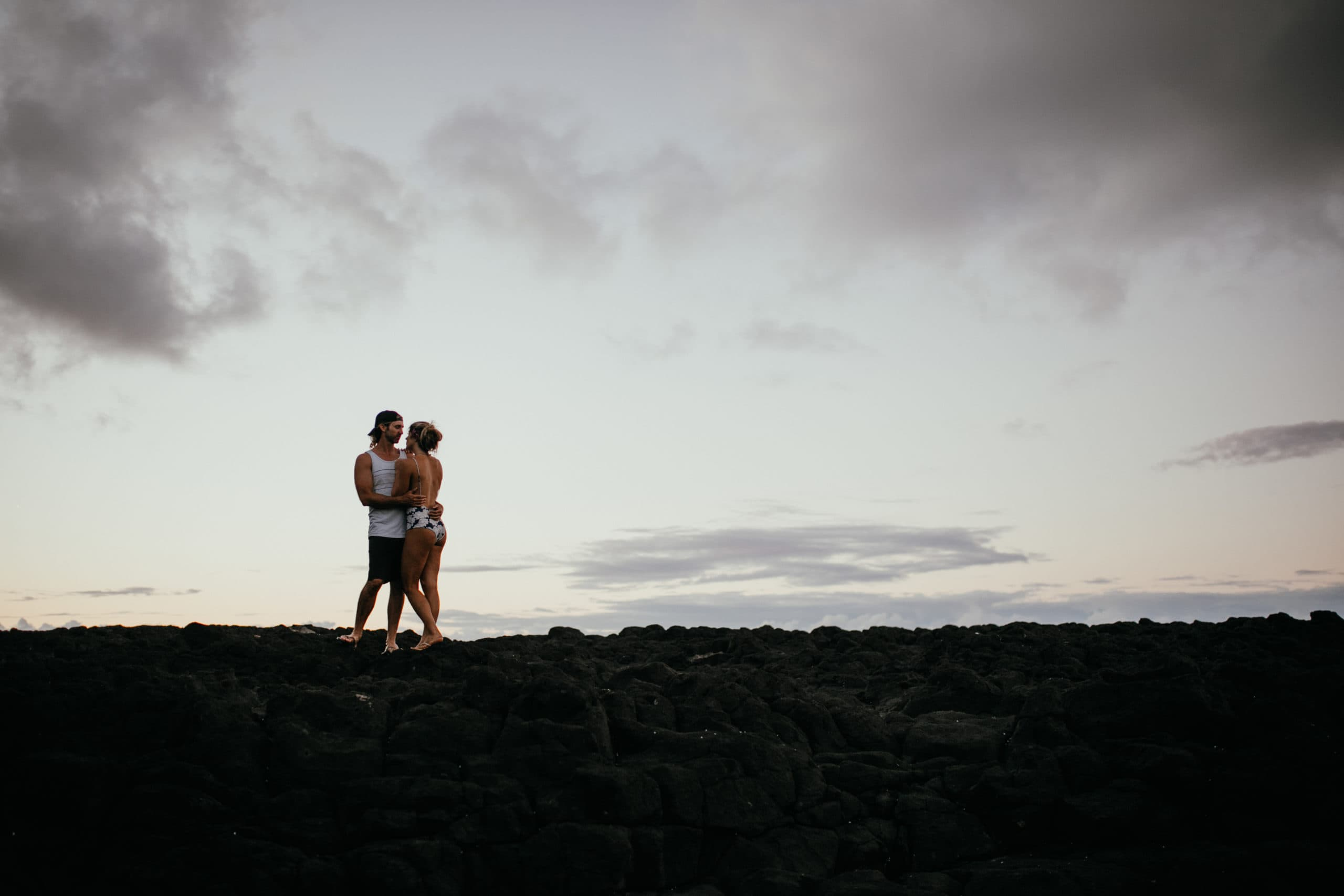 Oahu Couples Photography, wide angle shot of couple standing on rocks next to the beach