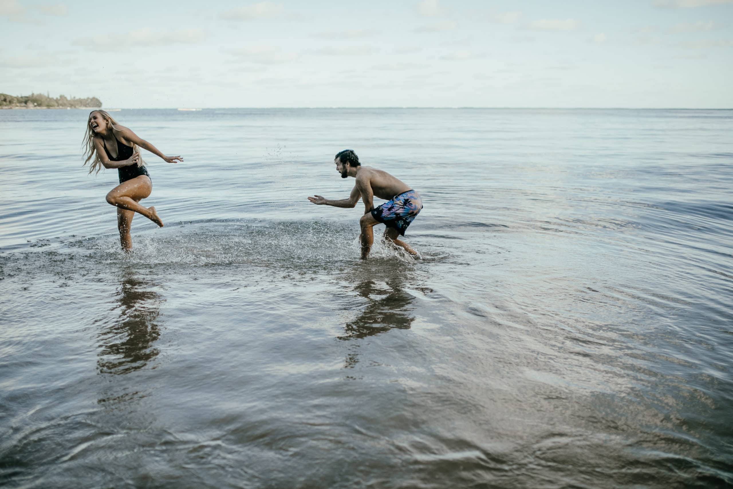 Oahu Couples Photography, man splashing woman as she runs away