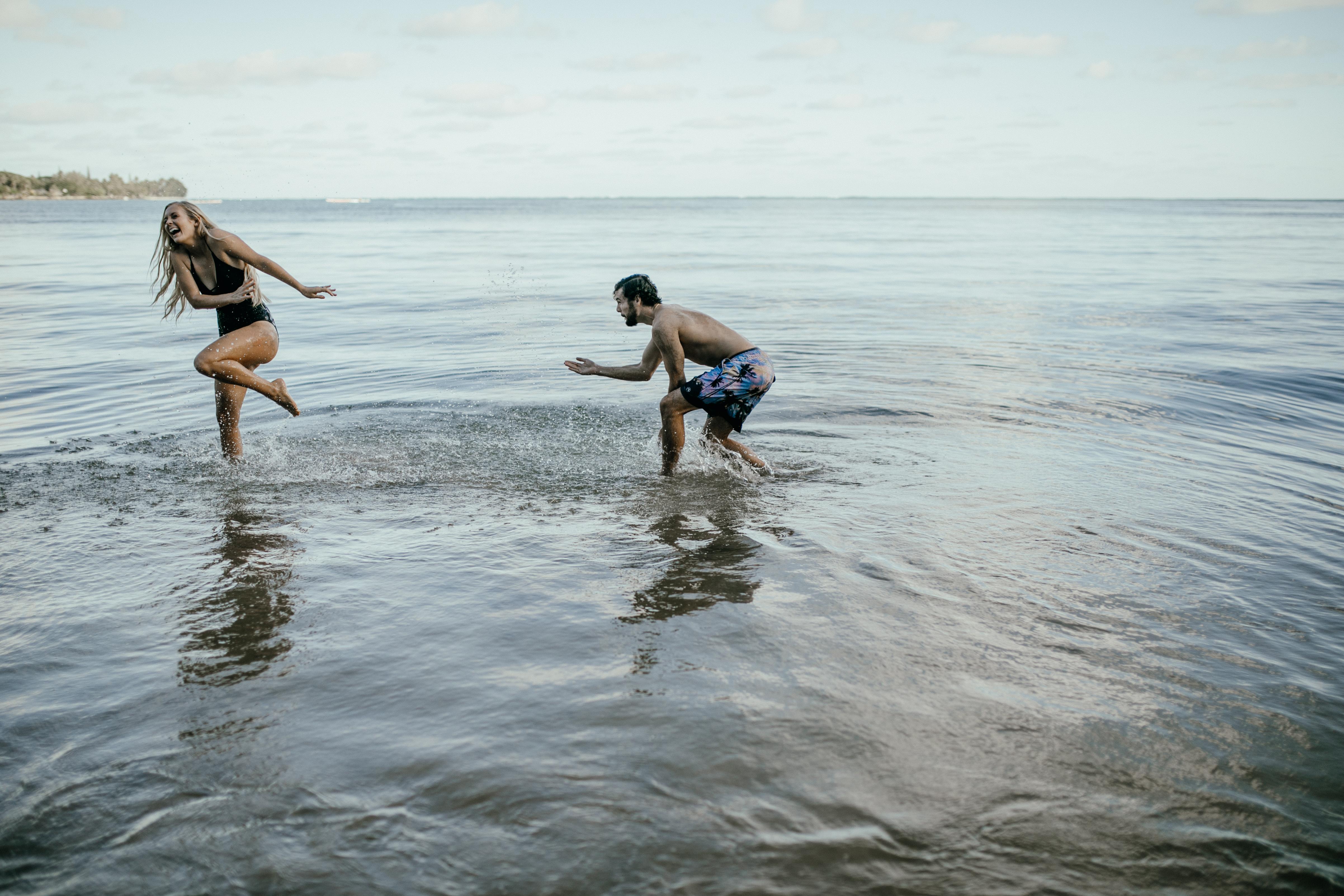 Oahu Couples Photography, man splashing woman as she runs away