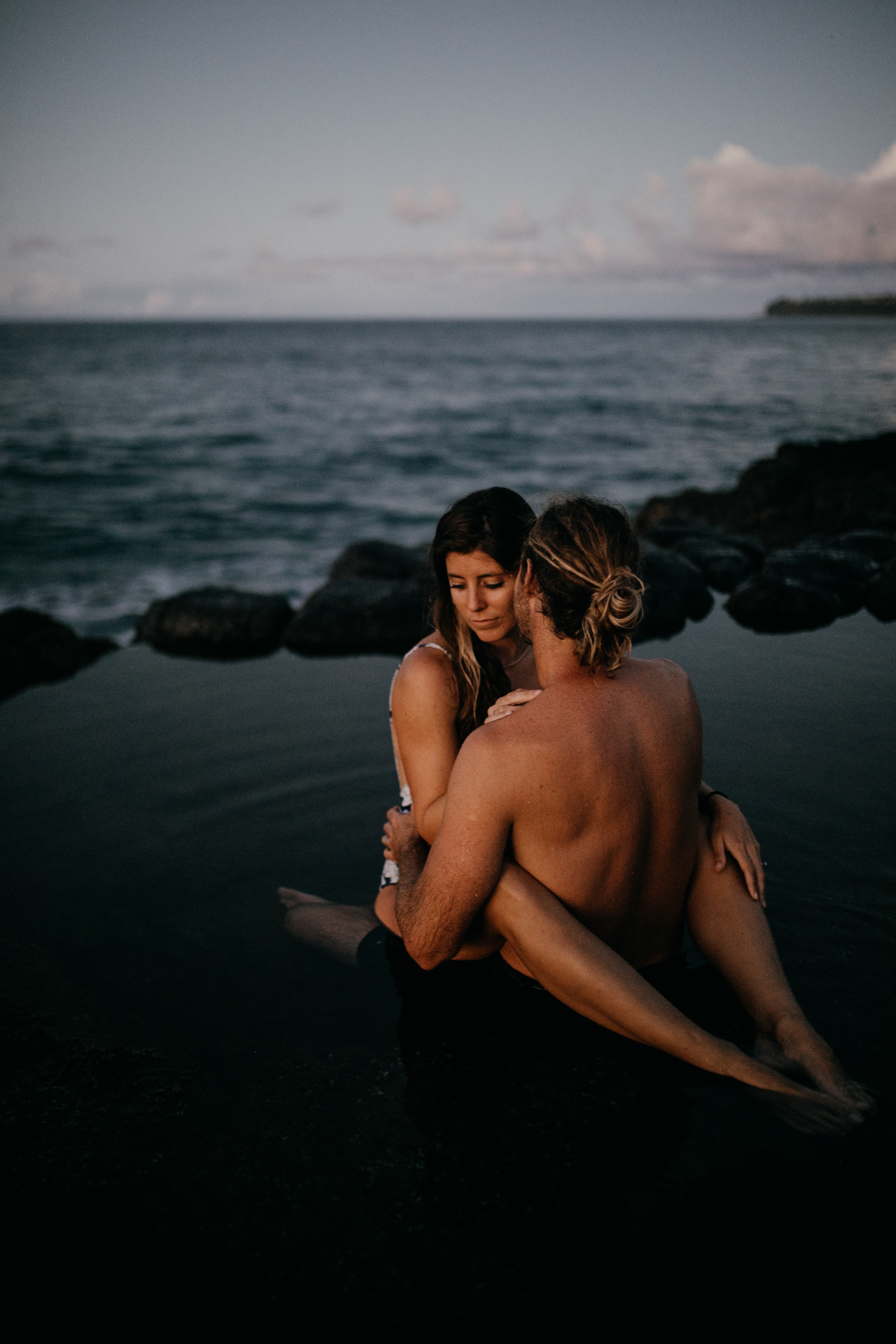 Oahu Couples Photography, couple sitting together in a pool of still water