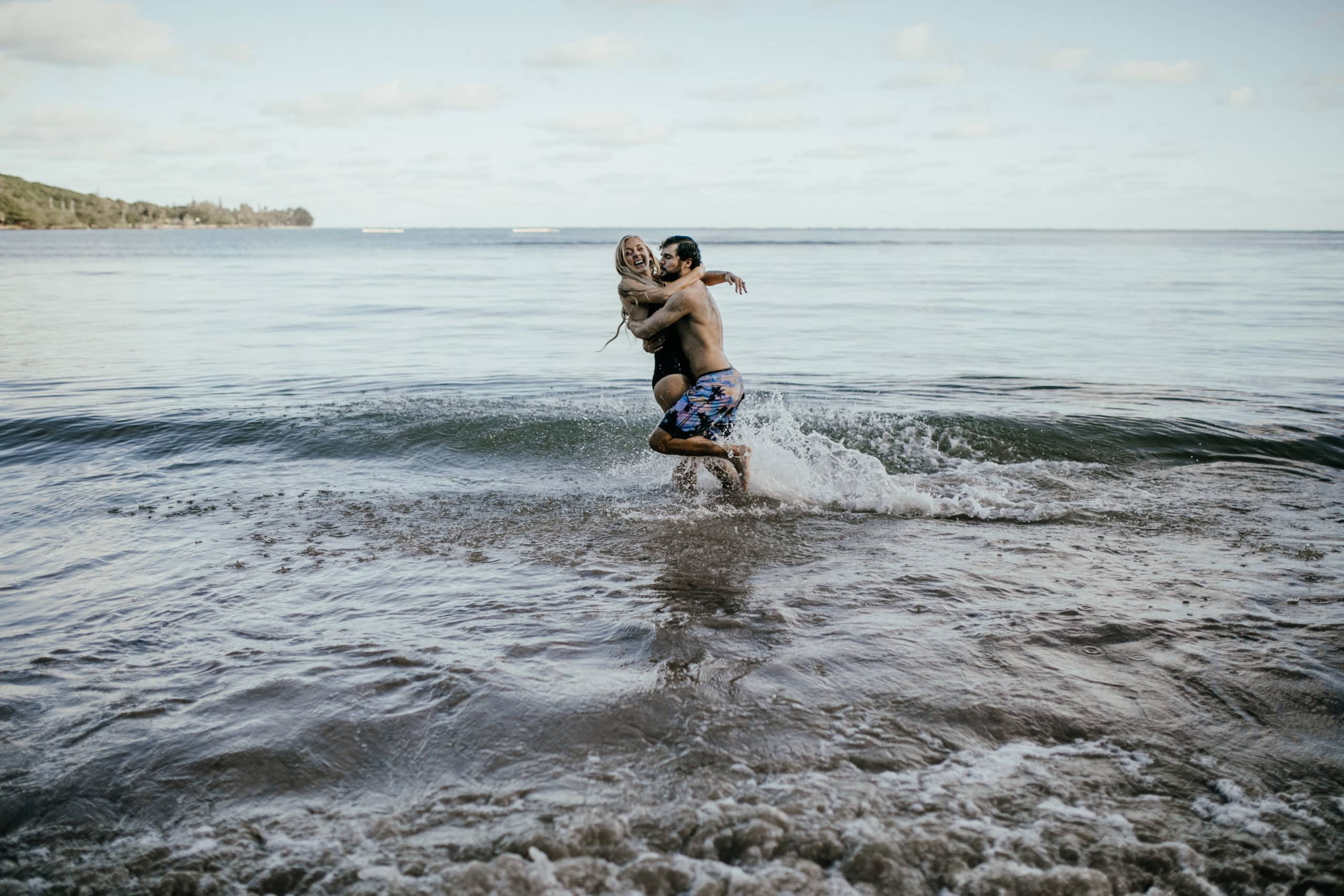 Oahu Couples Photography, couple playing and holding each other in the ocean