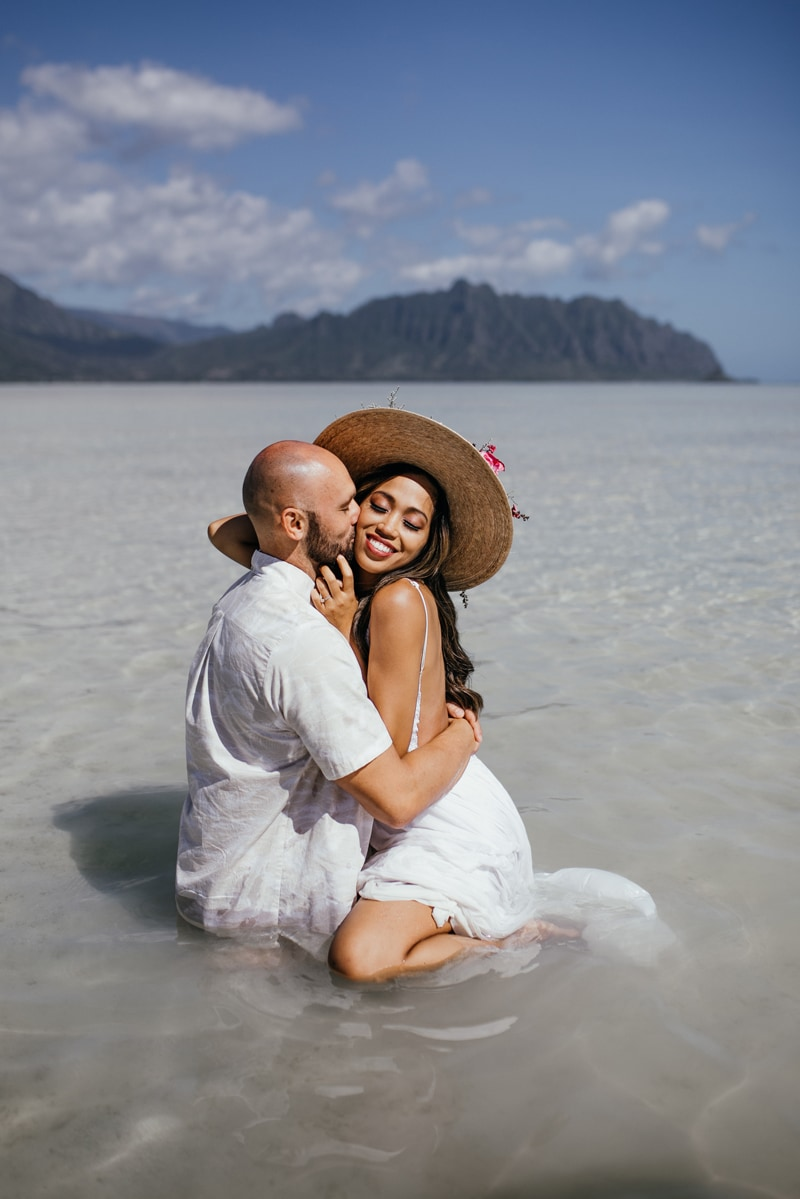 Oahu Couples Photography, man kissing woman's cheek as they kneel in the sand
