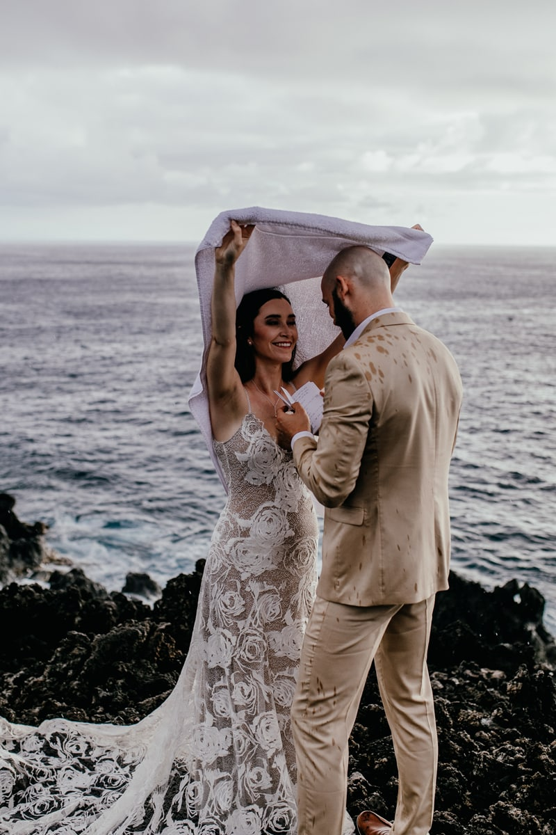 Oahu Wedding Photography, bride covering up grooms head from the rain