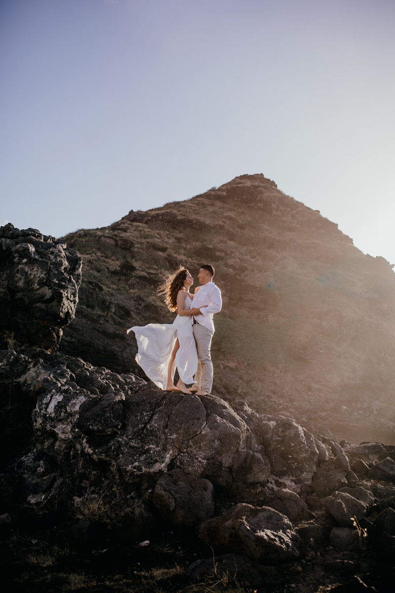 Oahu Wedding Photography, couple standing in the wind on the side of a cliff