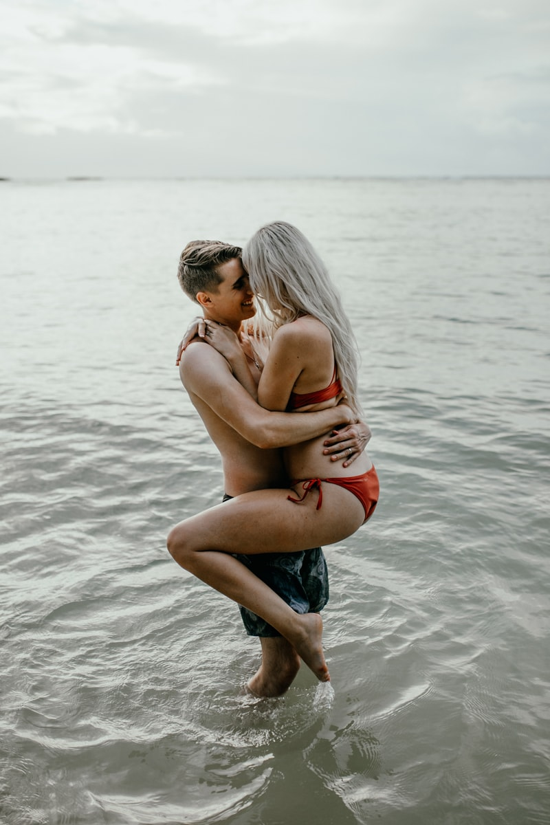 Oahu Couples Photography, man holding up woman around her waist standing in the ocean