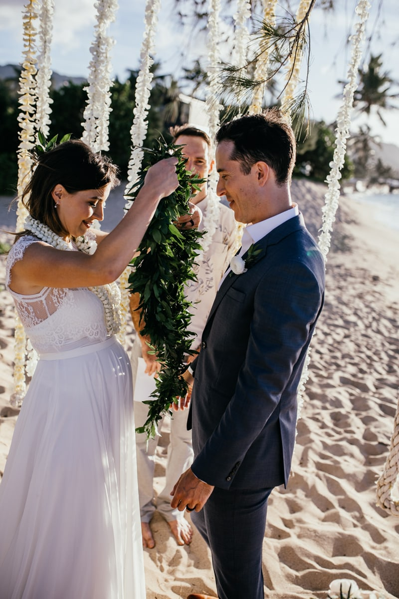 Oahu Wedding Photography, bride putting a leave lei over groom's head