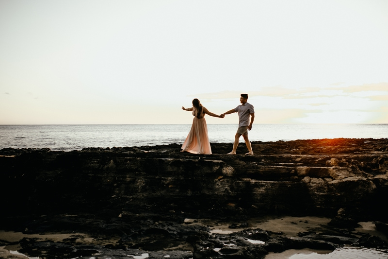 Oahu Couples Photography, wide angle shot of couple walking along the rocks at the beach during sunset