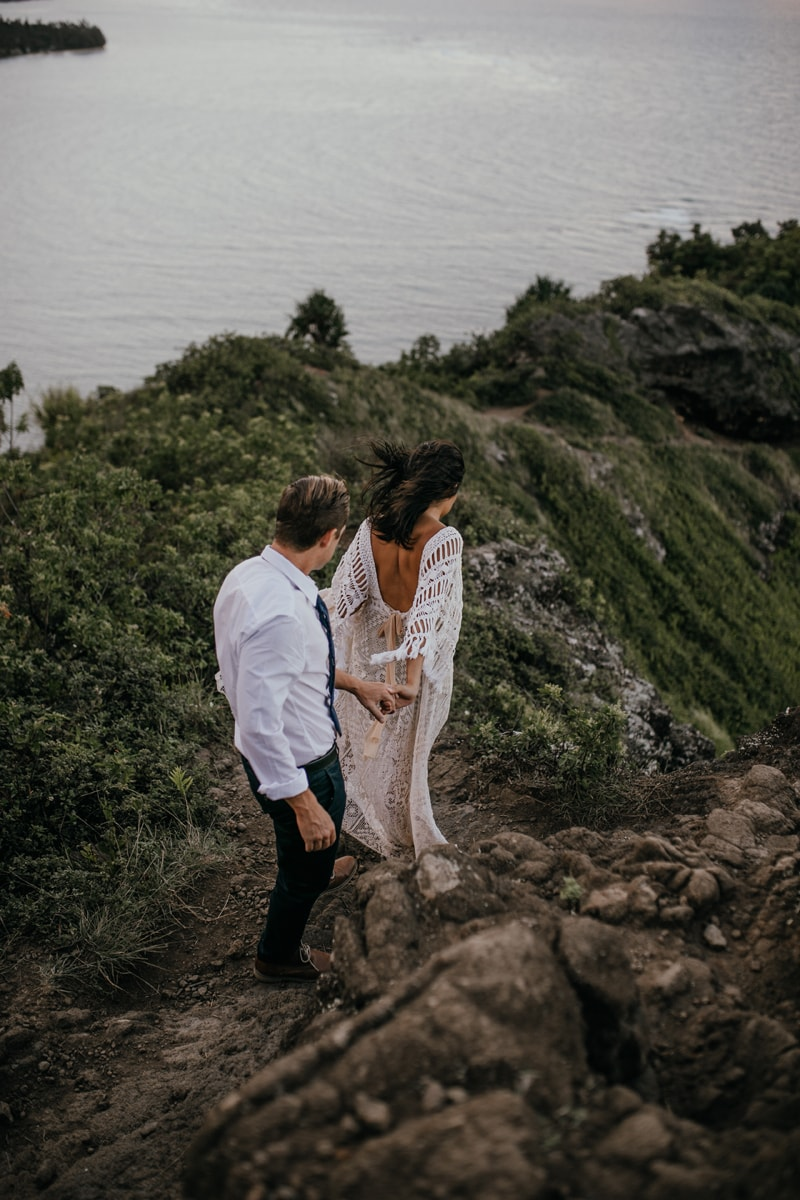 Oahu Wedding Photography, couple carefully walking down a dirt path to the beach