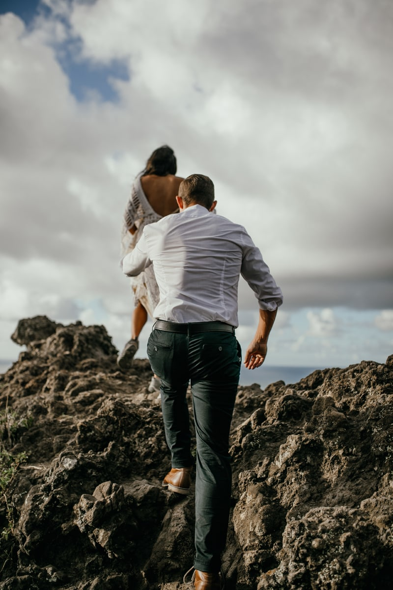 Oahu Wedding Photography, couple stepping up onto rocks next to the ocean