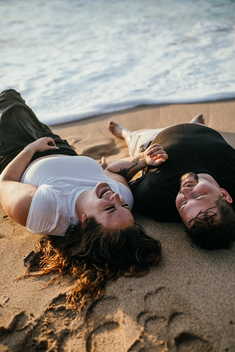 Oahu Couples Photography, couple laying in the sand laughing together