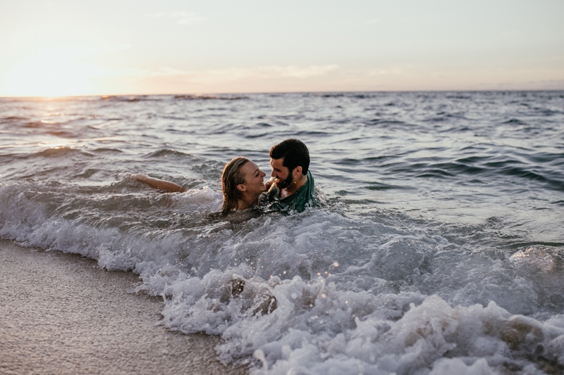 Oahu Couples Photography, couple laying in the waves looking at eachother