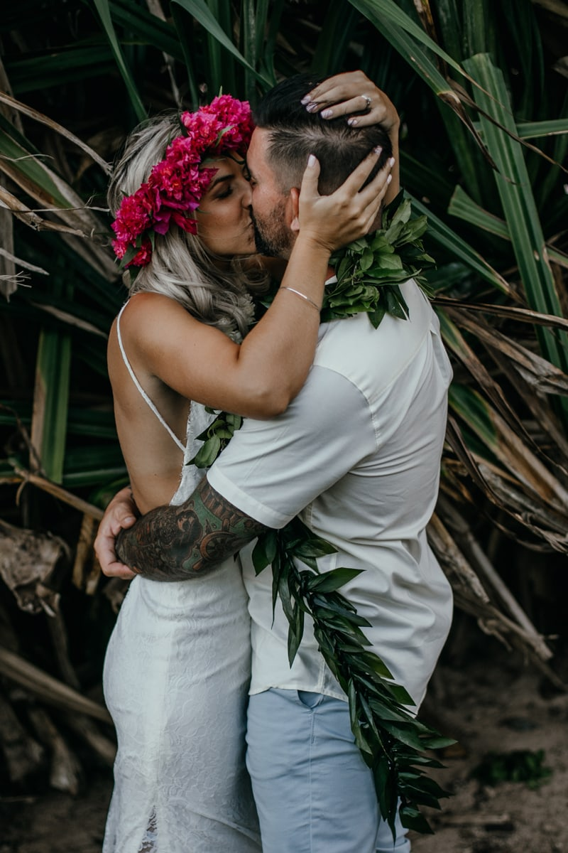 Oahu Wedding Photography, couple kissing in front of tall plants