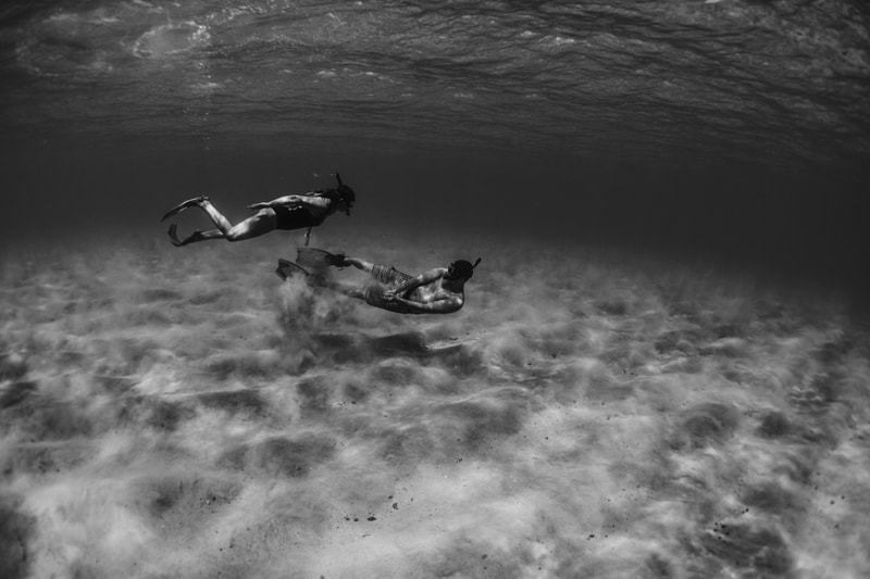 Oahu Couples Photography, black and white underwater shot of couple swimming together