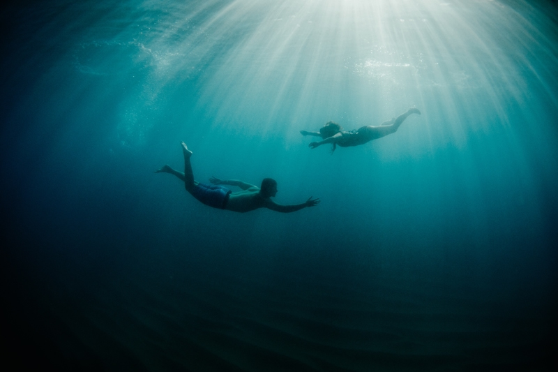 Oahu Couples Photography, underwater shot of man and woman swimming together