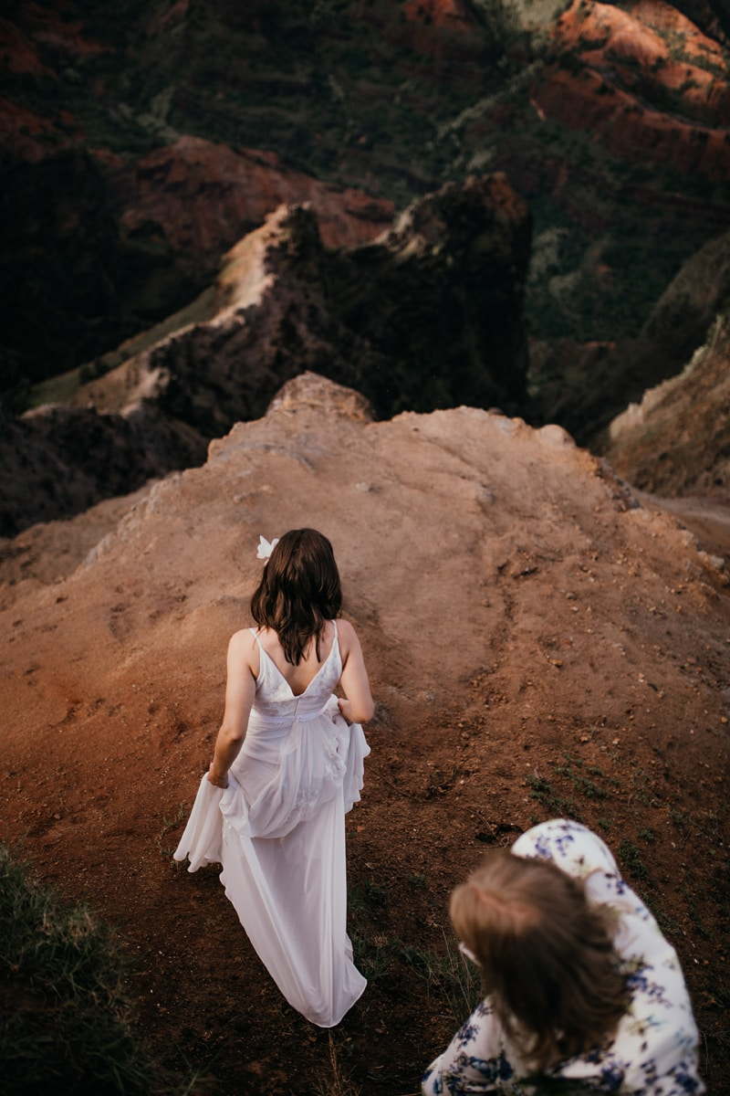 Oahu Wedding Photography, bride and groom climbing up to a cliff side