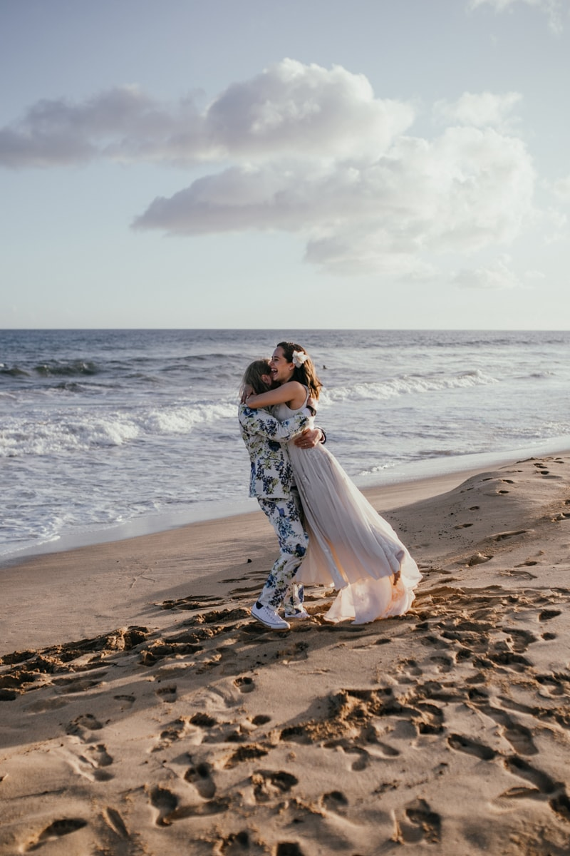 Oahu Wedding Photography, groom holding up bride for a kiss next to the ocean