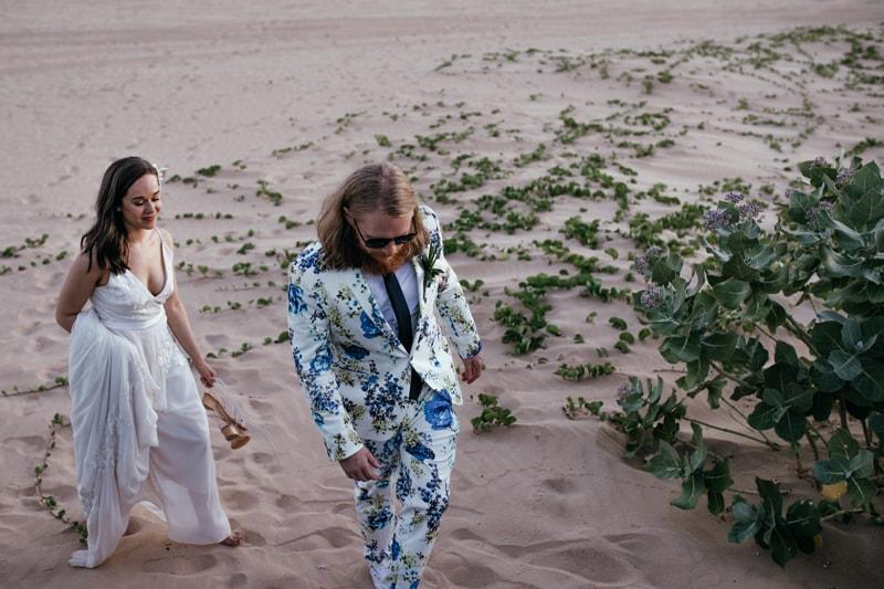 Oahu Wedding Photography, groom walking up a sandy ridge