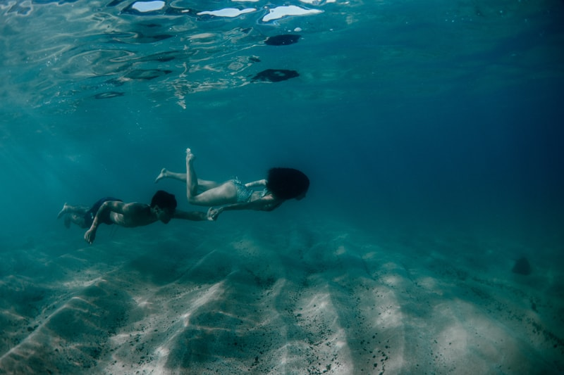 Oahu Couples Photography, underwater shot of couple swimming in a row together