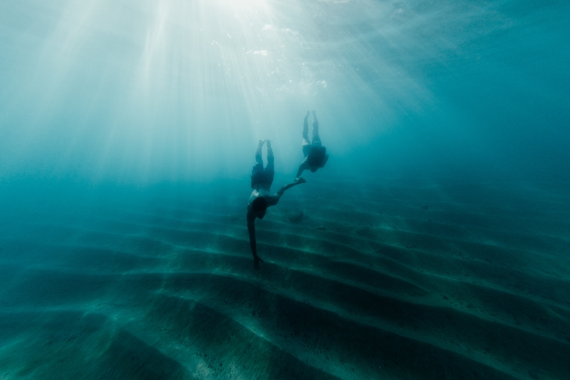 Oahu Couples Photography, underwater shot of couple swimming toward the ocean floor