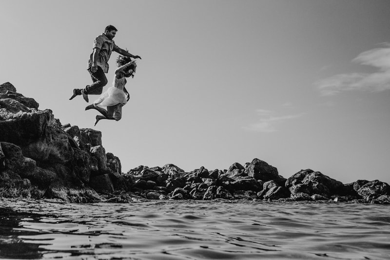 Oahu Wedding Photography, black and white of couple jumping into the water