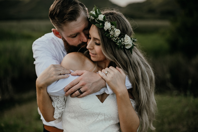 Oahu Wedding Photography, groom with his arms wrapped around bride wearing a flower crown