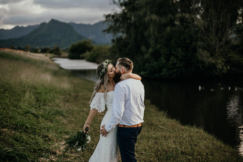 Oahu Wedding Photography, couple standing kissing with their arms around each other