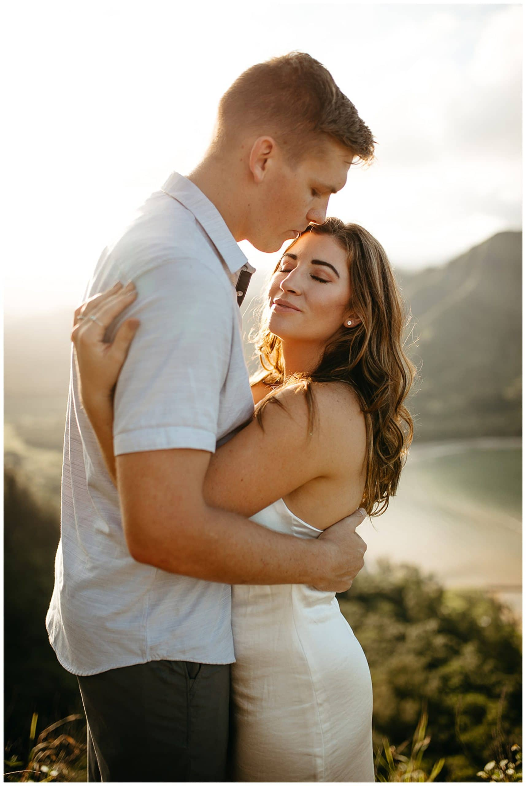 husband kissing wife's head at sunset