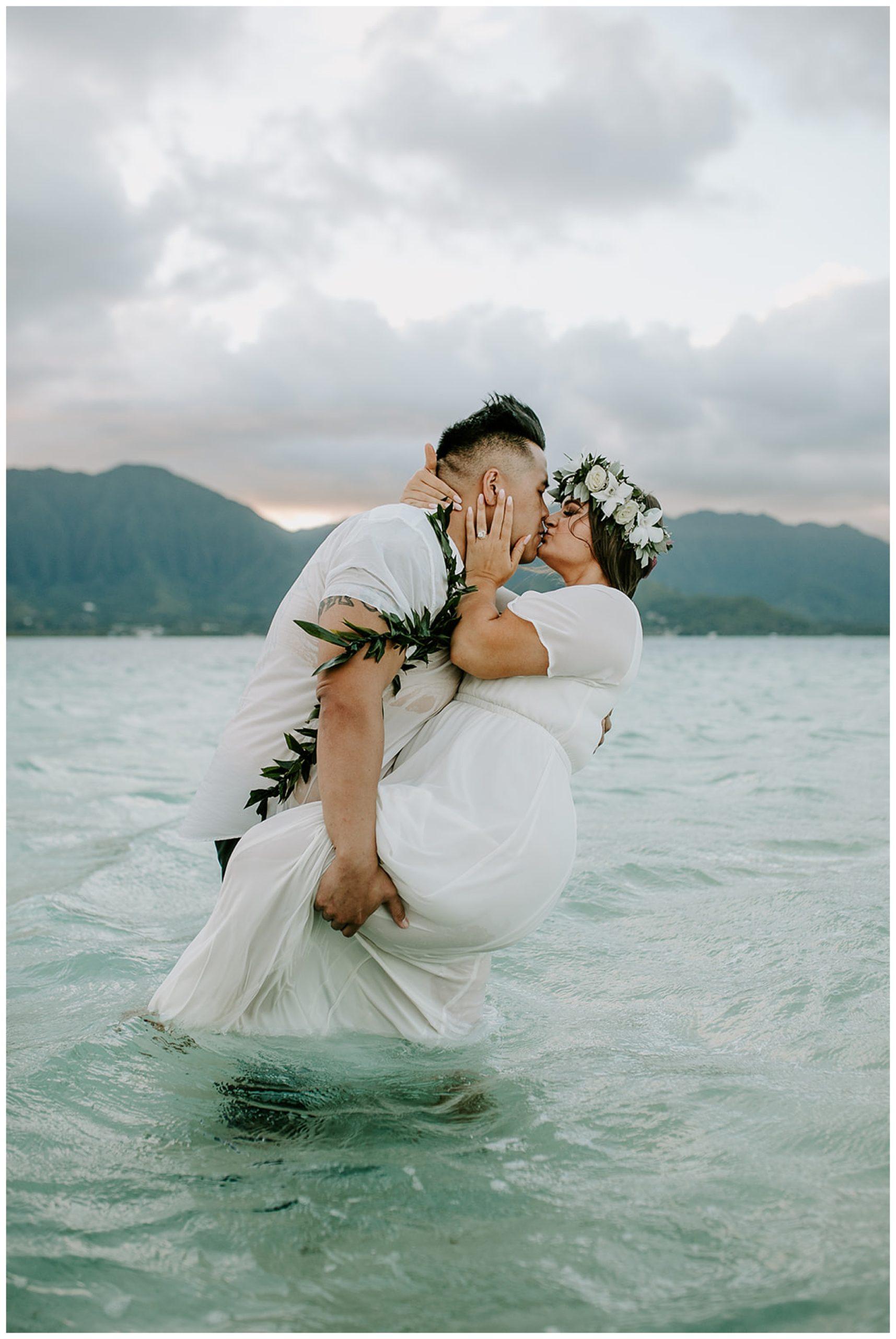 groom dip kissing bride in ocean