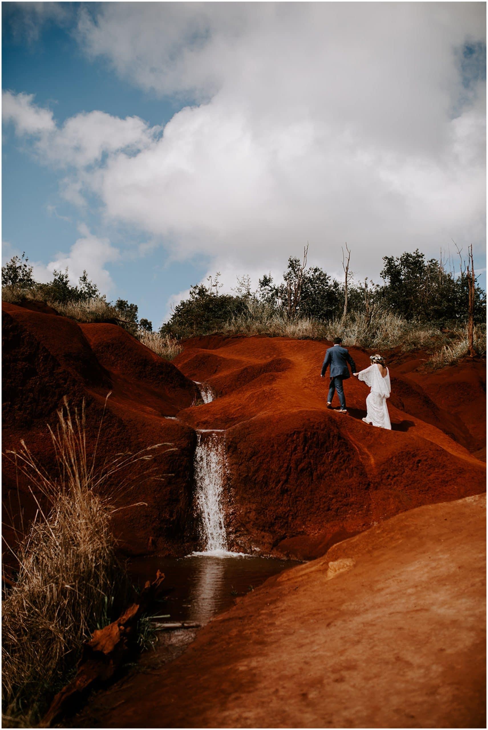 bride and groom walking by waterfall