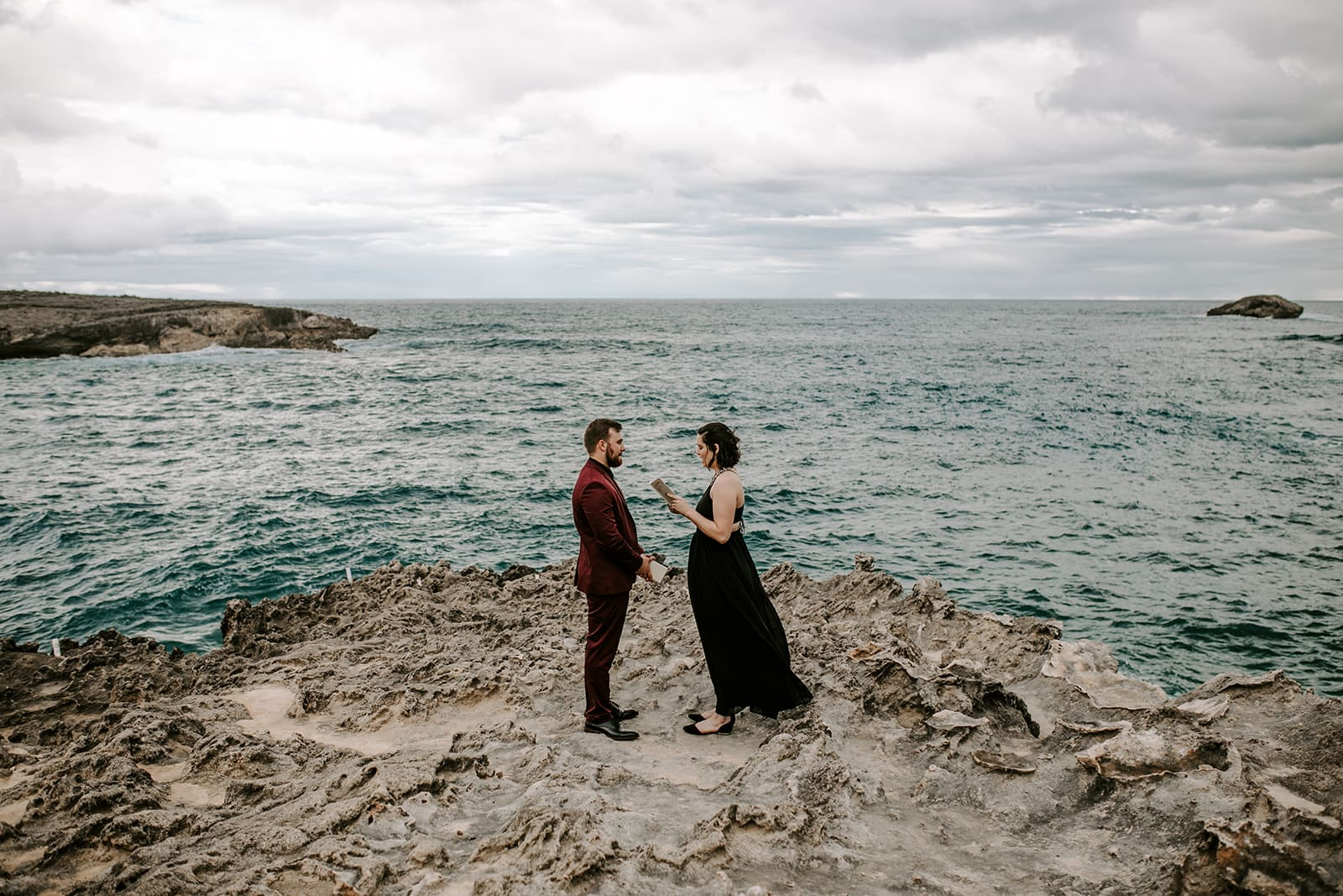 couple reading vows to each other on beach