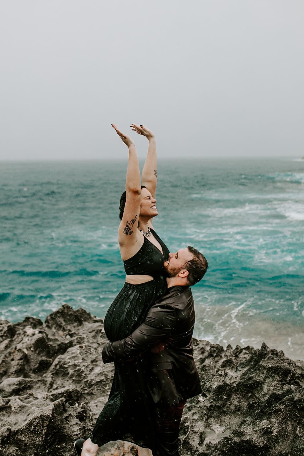 couple dancing on the beach in the rain