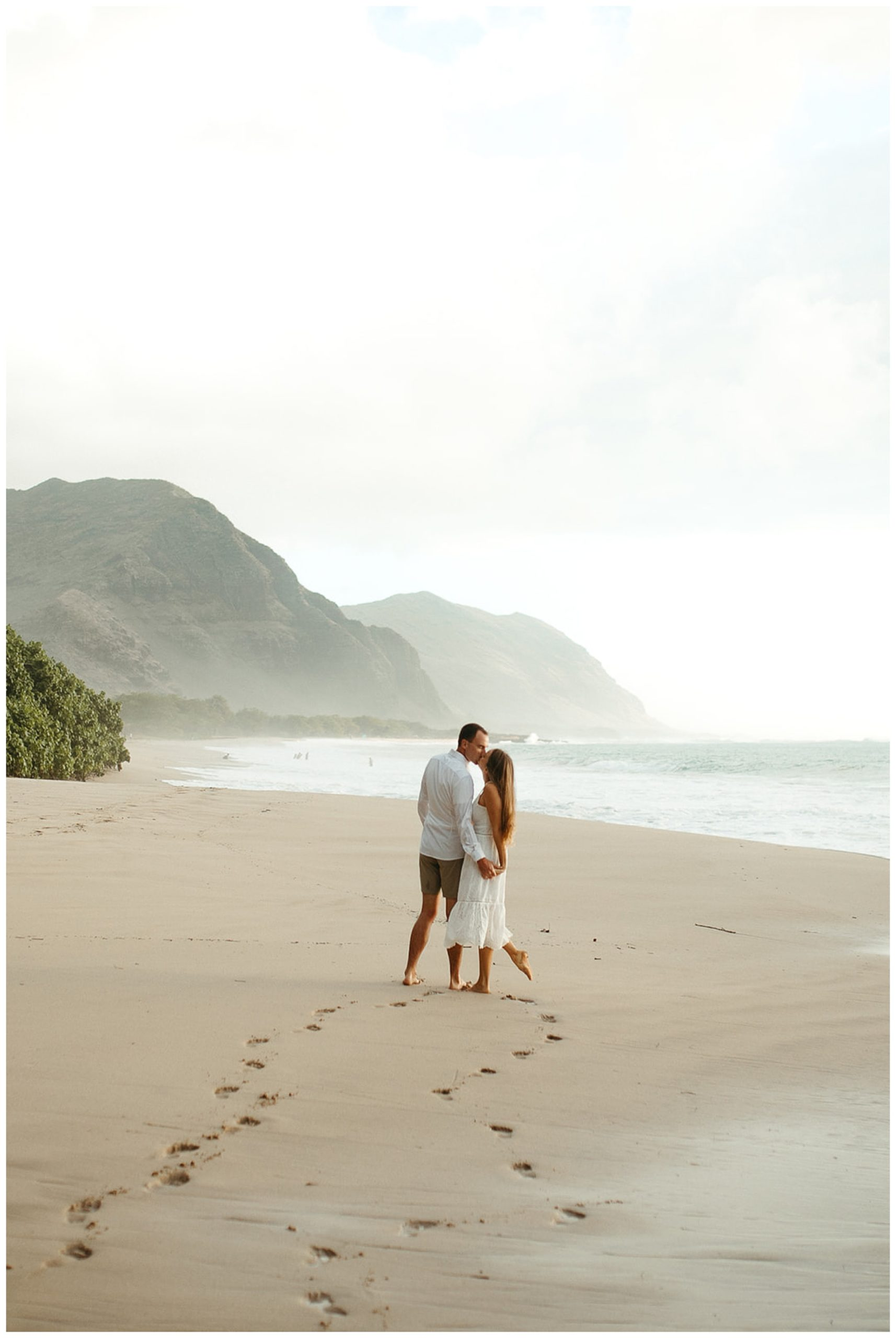 couple kissing on beach in hawaii
