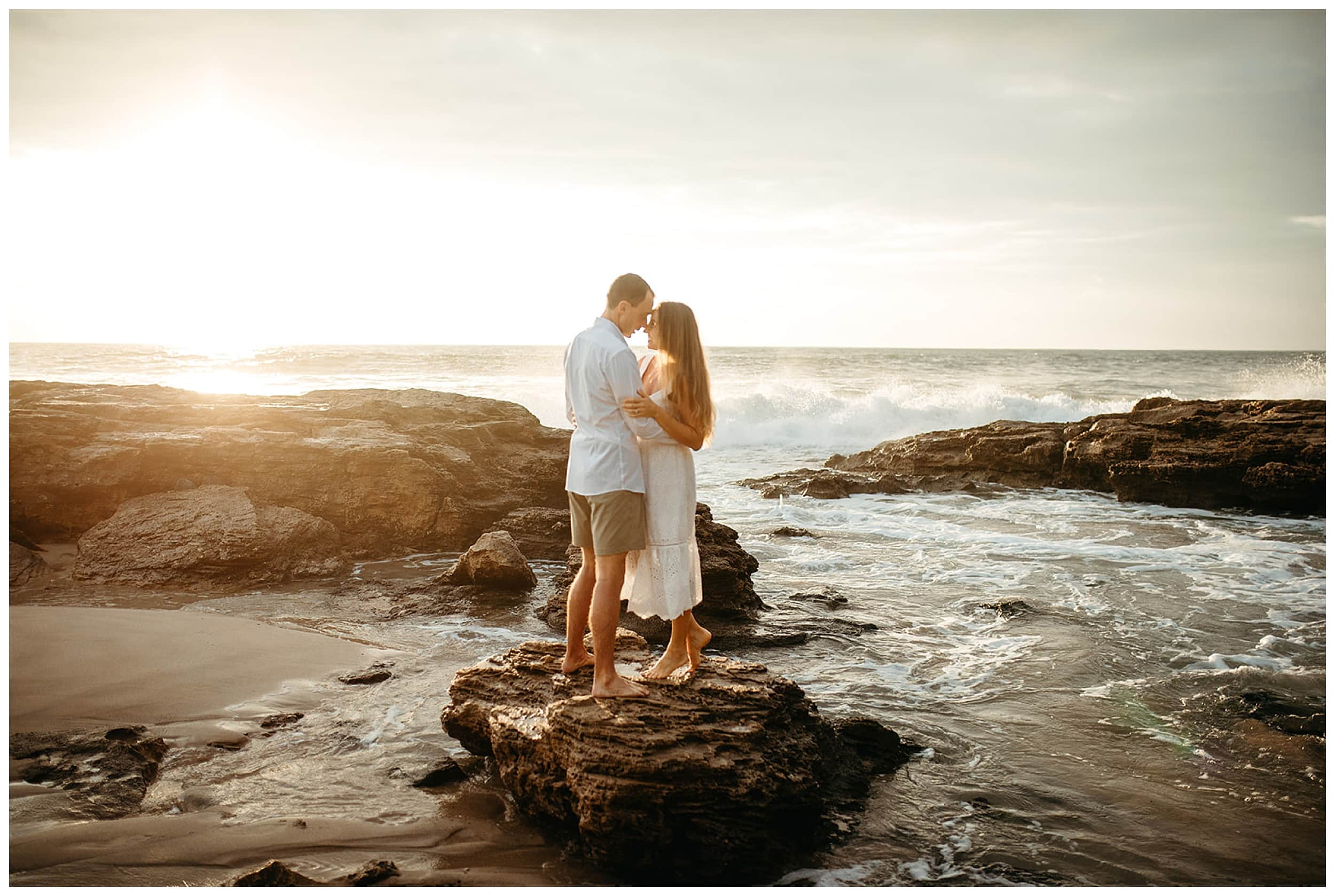 couple kissing on rocks in hawaii