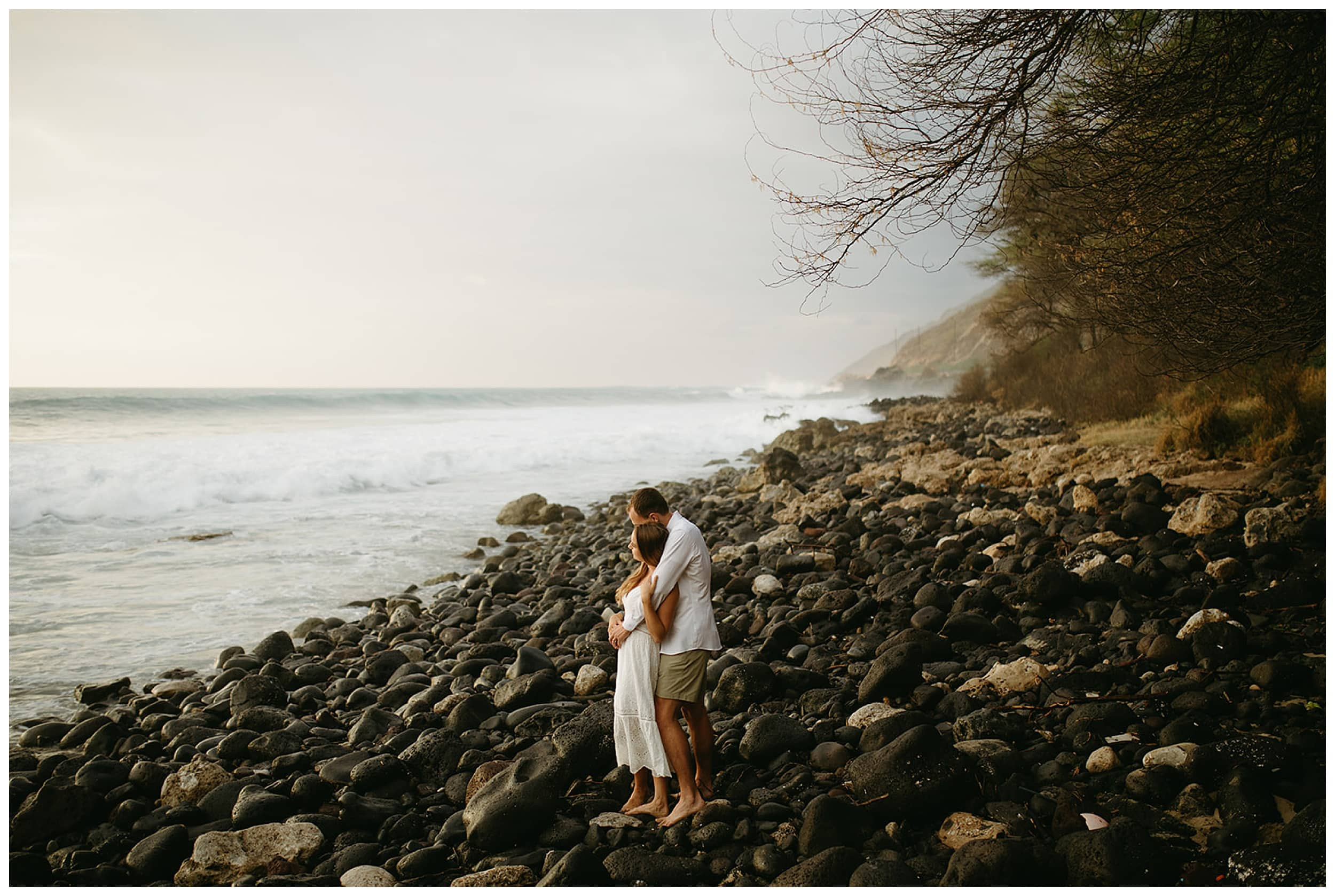 couple hugging on rocks by beach