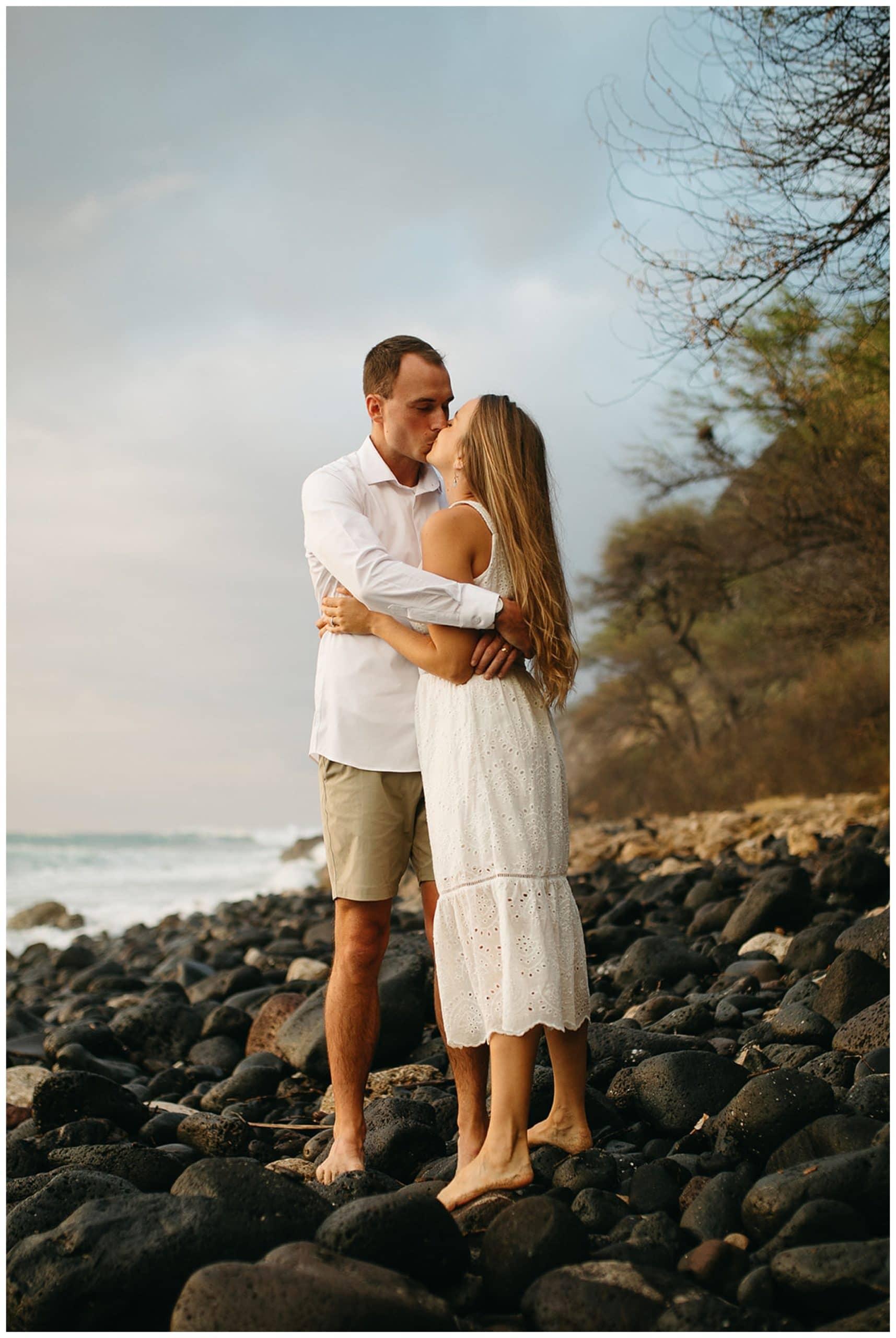 couple kissing on rocks on beach