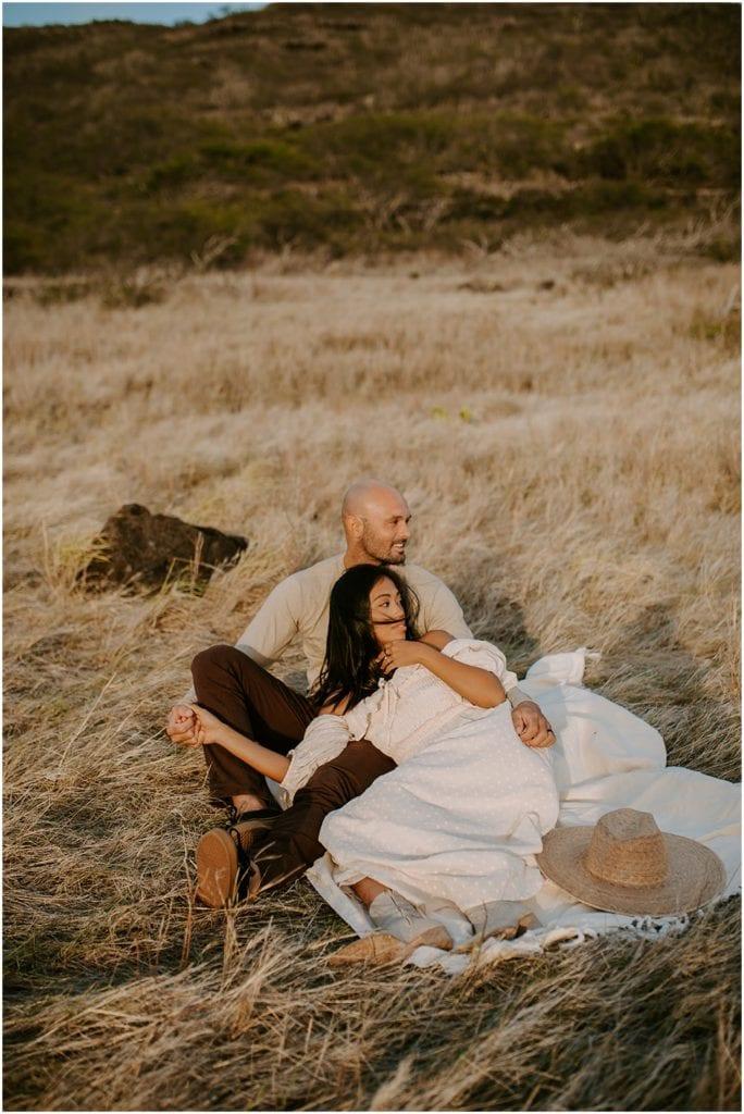 woman laying in man's lap on mountain