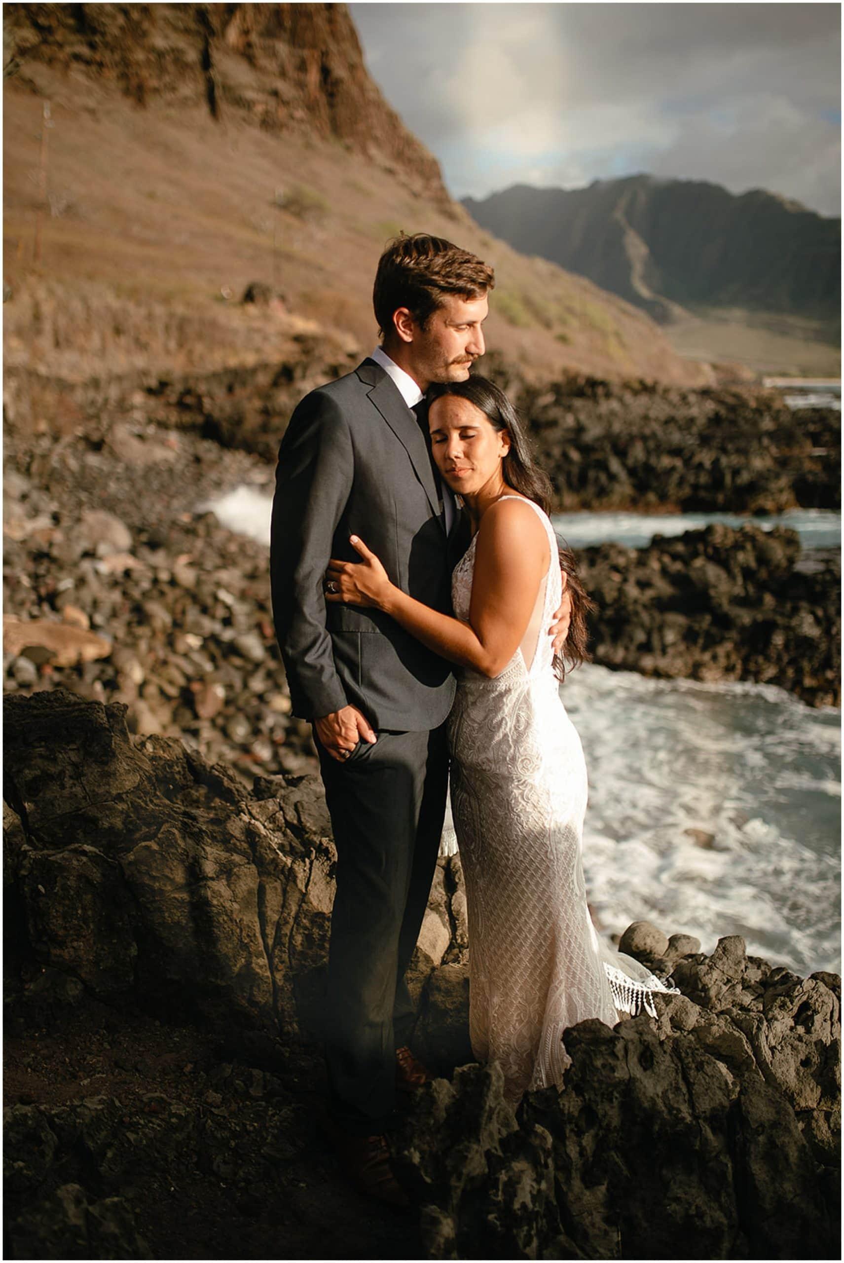 bride and groom hugging on rocks