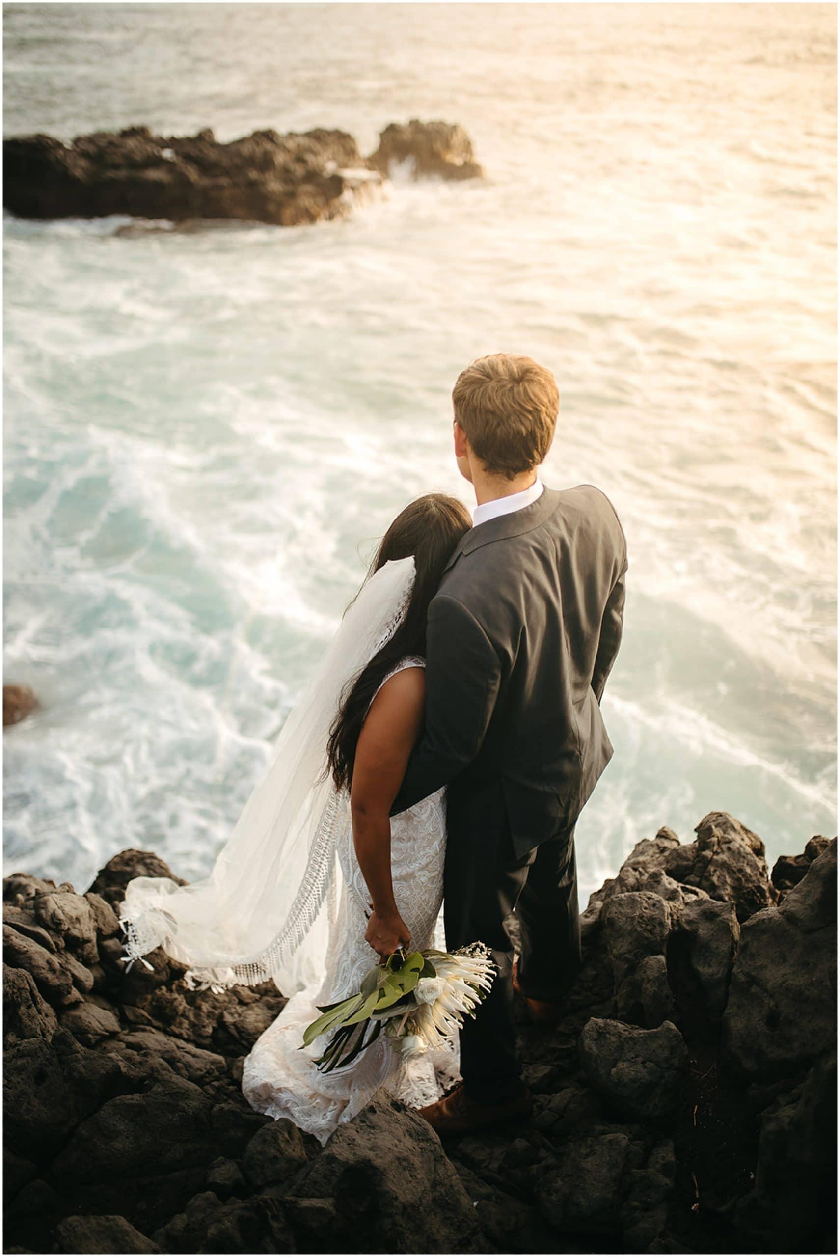 bride and groom watching ocean waves