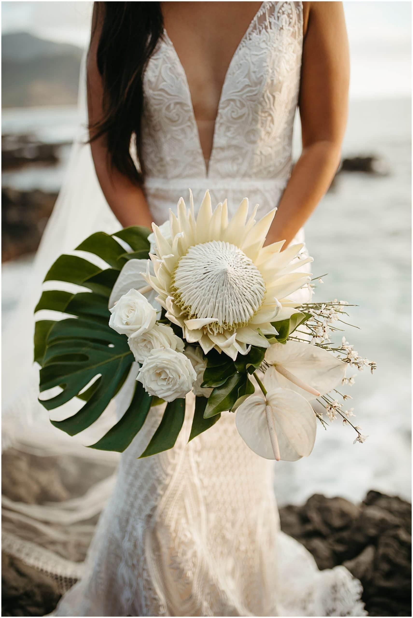 bride holding tropical floral bouquet