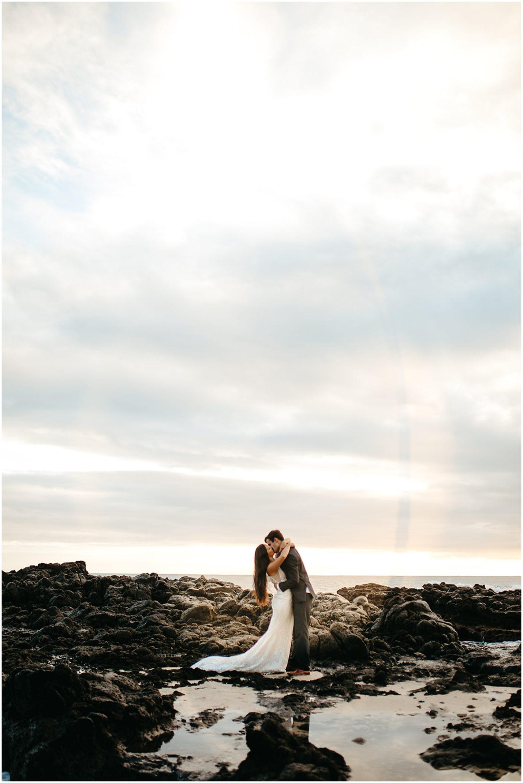 groom dip kissing bride on beach