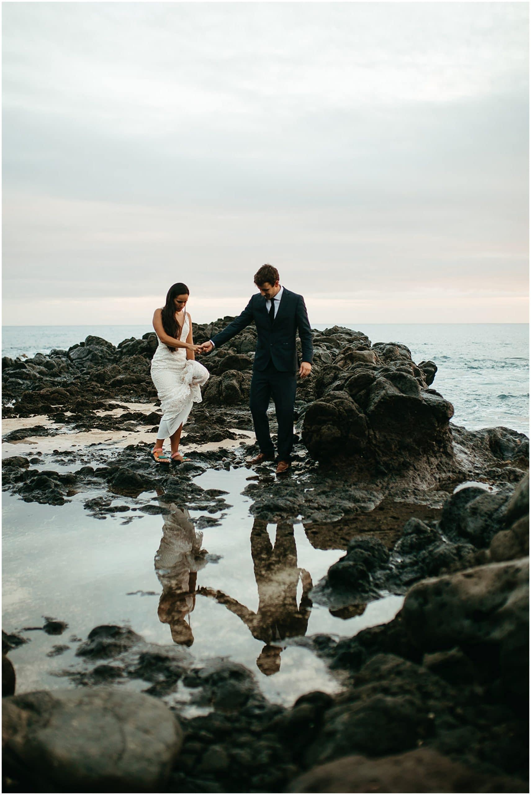 bride and groom walking in tidepools